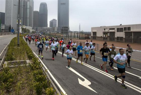 Participants run past Two International Finance Centre (IFC), as they compete in the Hong Kong marathon