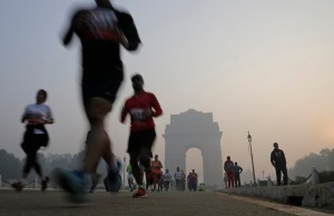 Participants run as the India Gate monument is seen in the hazy background during Delhi Half Marathon in New Delhi, India, Sunday, Nov. 29, 2015. Ethiopia's Birhanu Legese and Kenya's Cynthia Limo won the men's and women's elite categories, respectively. (AP Photo/Altaf Qadri)